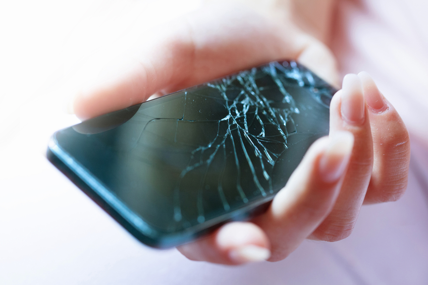 A black smartphone with a broken screen in a female's hand. The smartphone has a crashed screen after it was dropped. A women holds the smartphone. The smartphone needs to get fixed to work again. Shallow depth of field with fokus on the broken glass